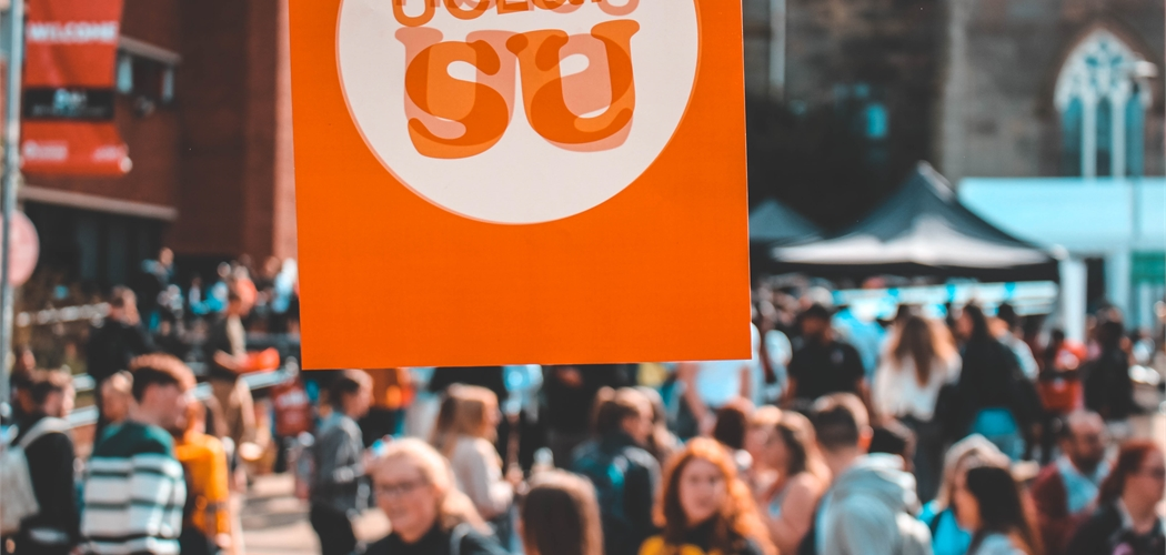 Students' Union logo on bunting hung above a crowd